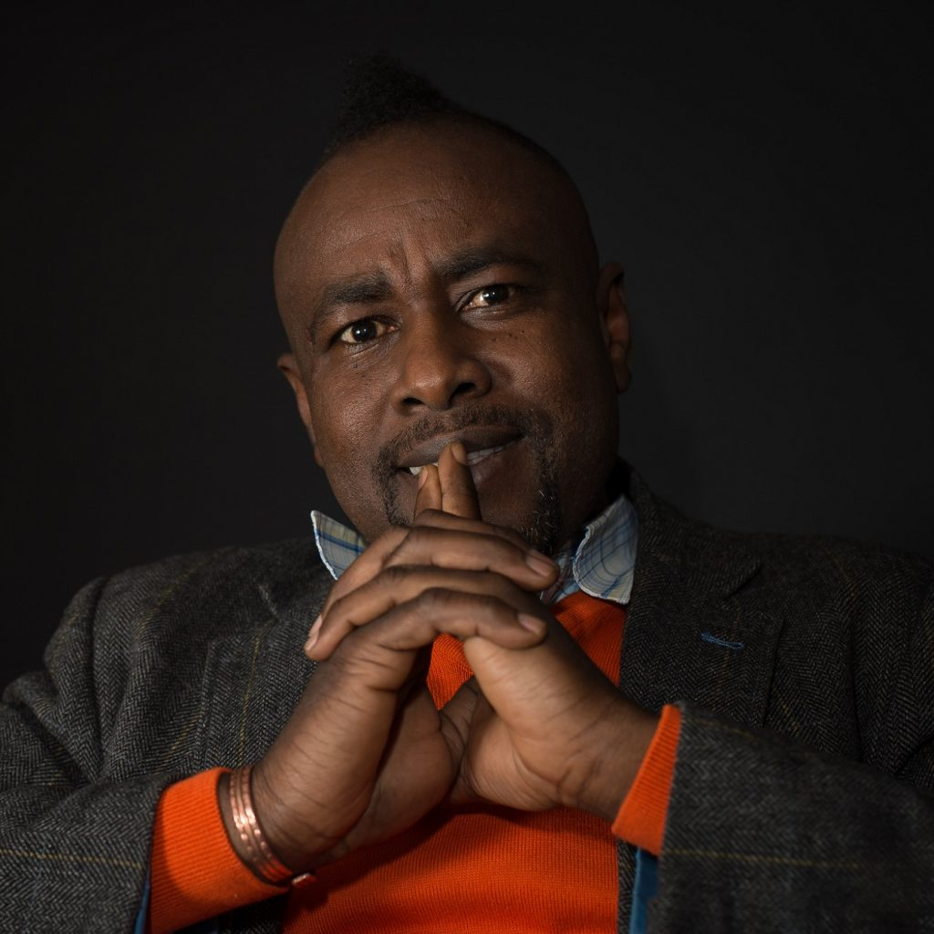 A black man looks pensively past the camera.