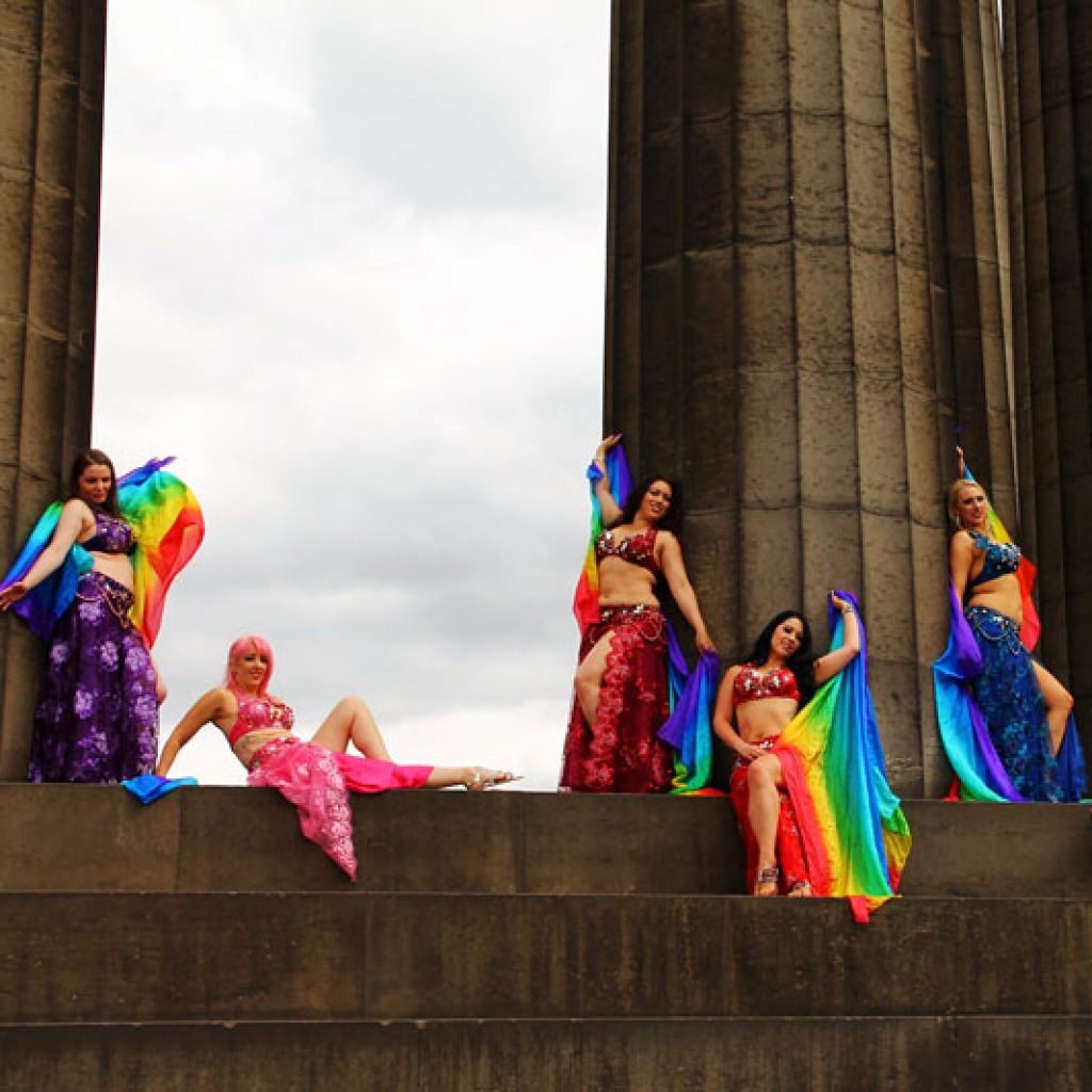 Image of 7 bellydancers wearing colourful costumes, sitting on a set of large stone steps
