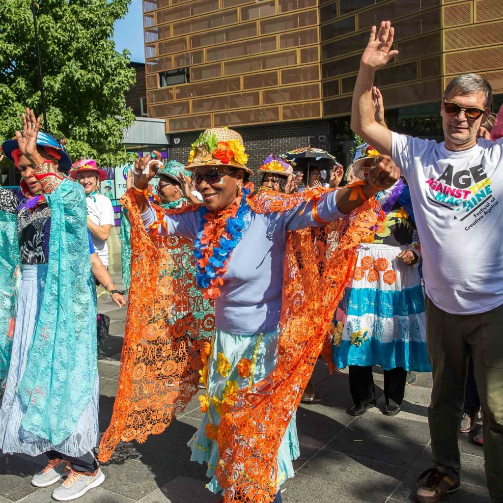 An group of older people in a carnival style parade, dressed to party in front of a blue sky.