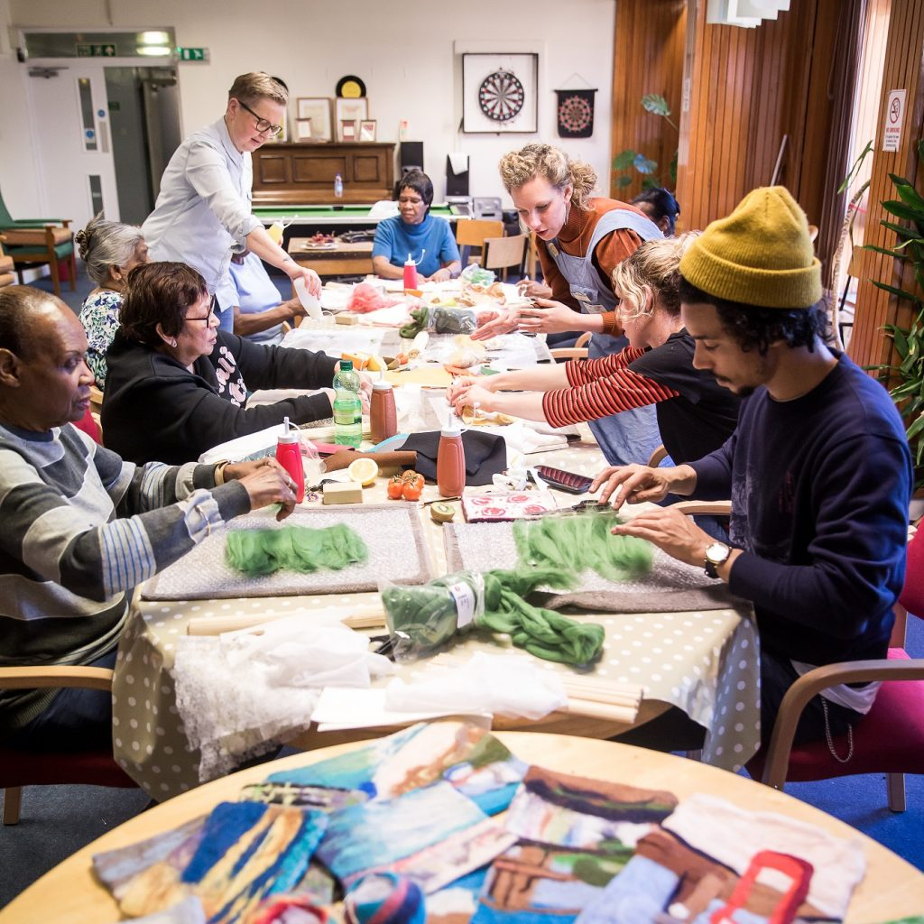 Adults of all ages sit working together on crafts at a long table.