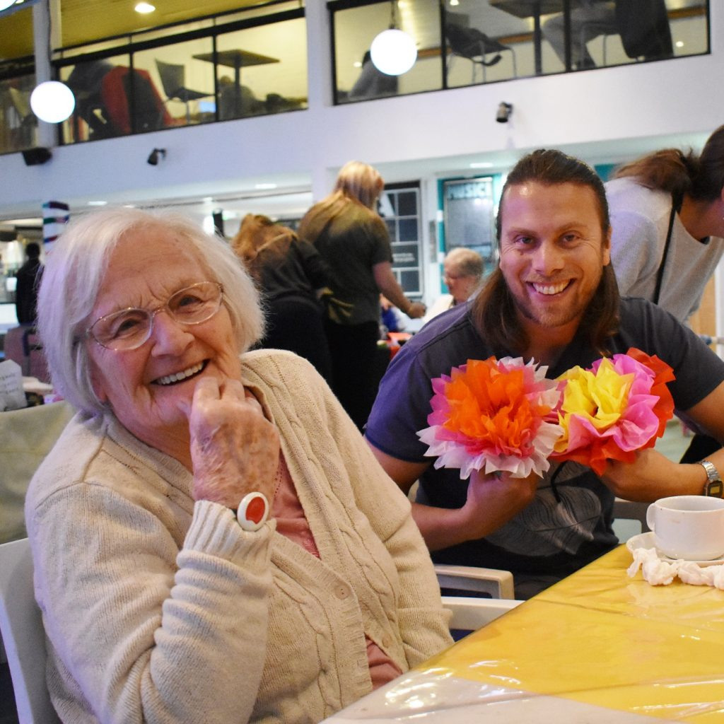 Older woman and younger man sit together with bright, tissue paper flowers and smile at the camera.