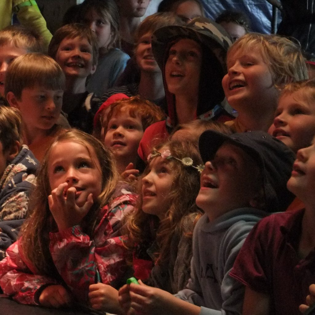 A group of a young children staring up at a stage looking engaged and laughing.