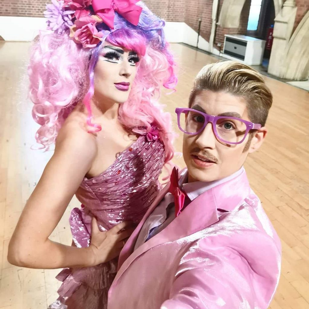 Image of drag queen and drag king dressed in different shades of pink