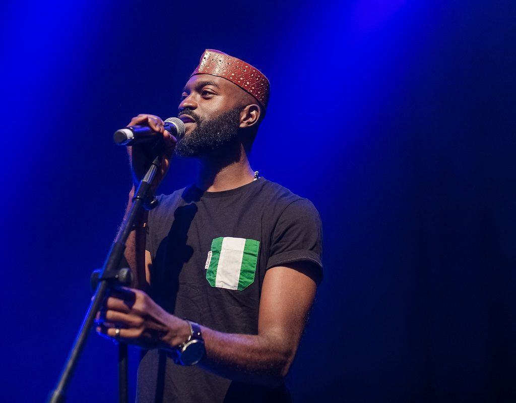 Image of Inua Ellams performing with a microphone