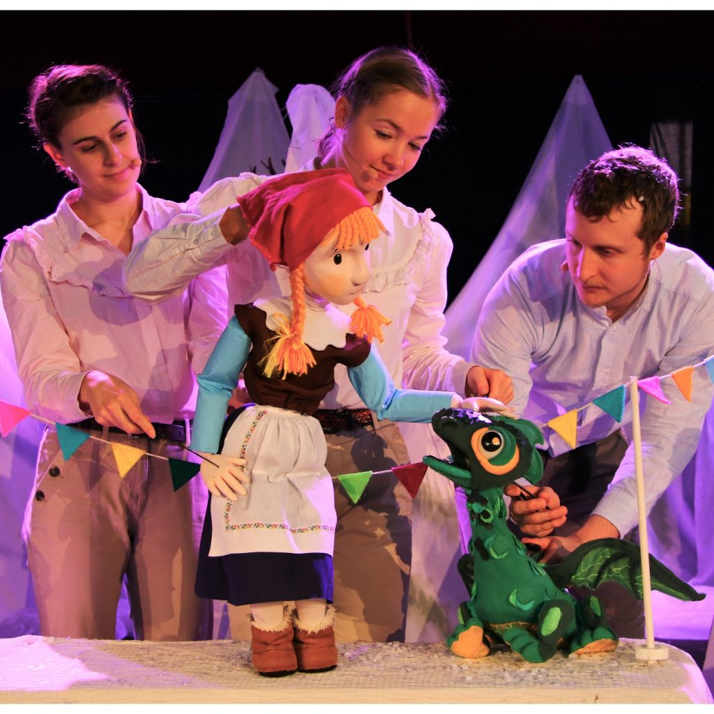 3 performers hold up a female puppet and a green dragon puppet