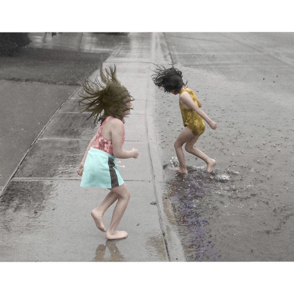 A young boy and girl play in the rain