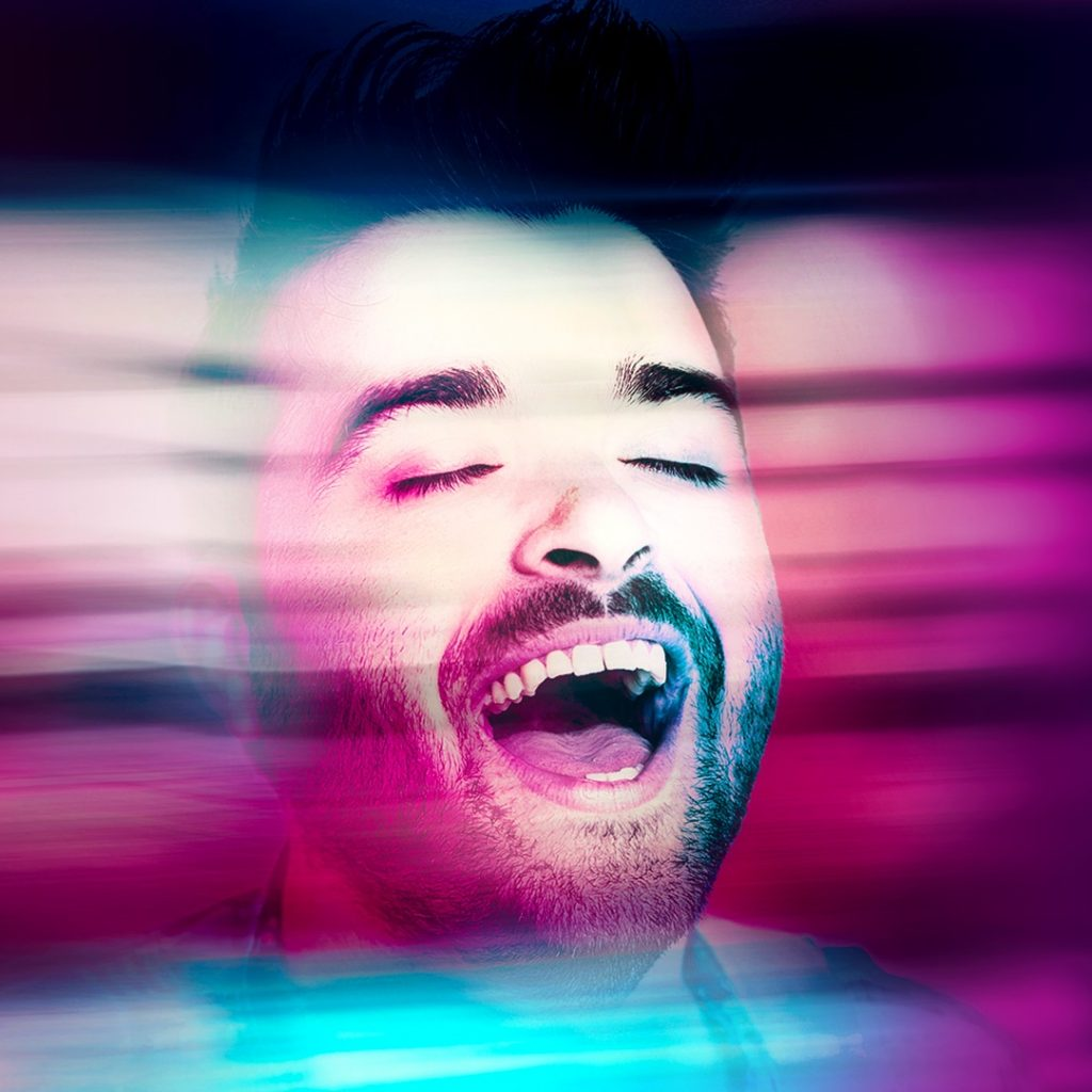 Image of a man's face, with his eyes closed and mouth open, in blurry purple and blue lighting