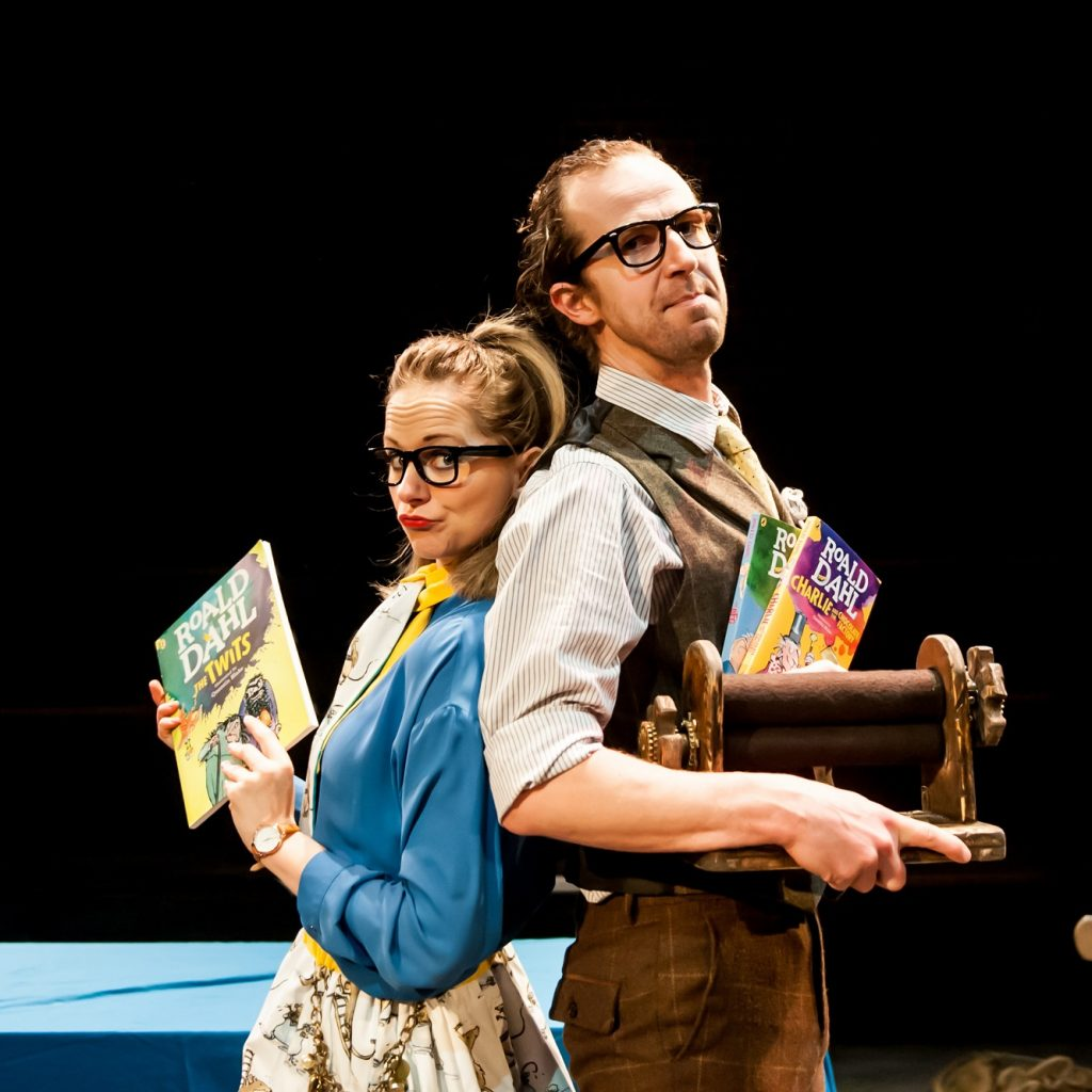A man and a woman both wearing glasses stand back to back while holding books