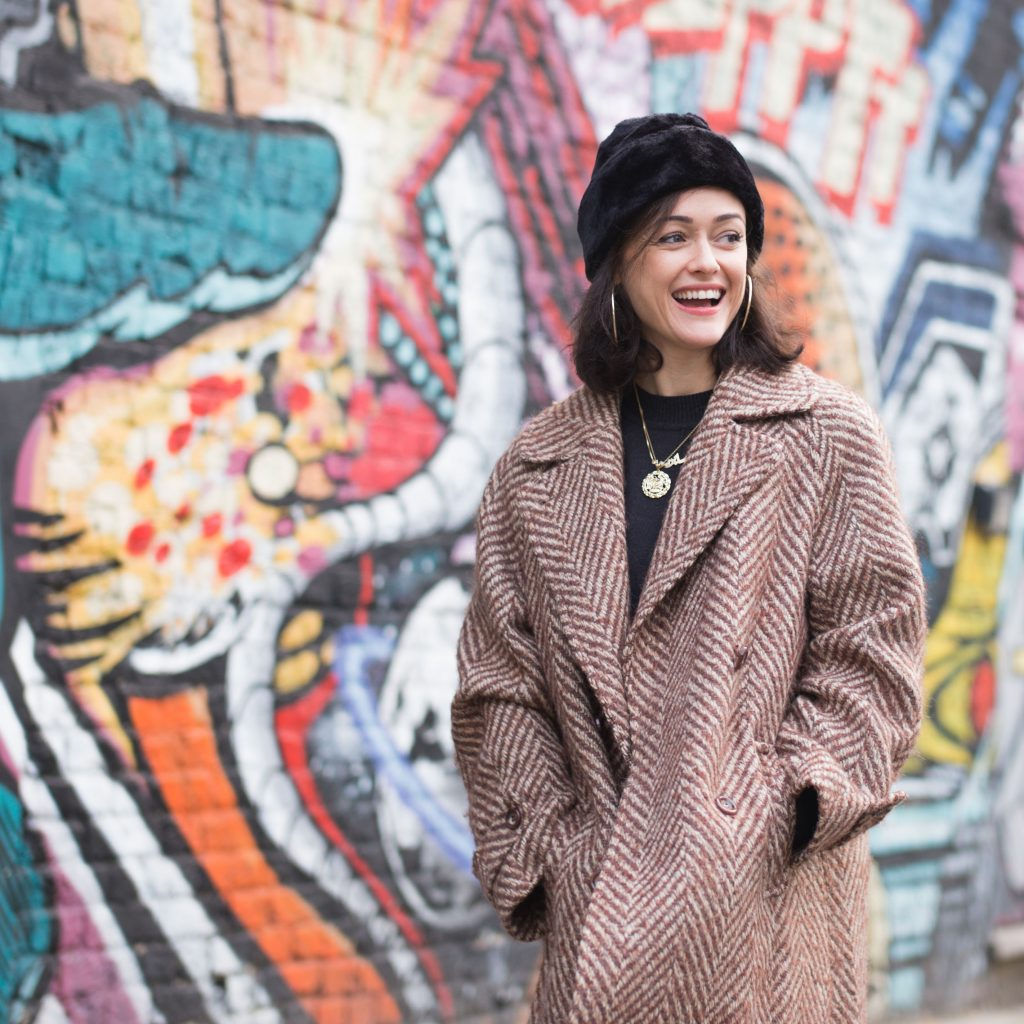 Image of Sabrina Mahfouz. Young woman in a coat and jacket is laughing.