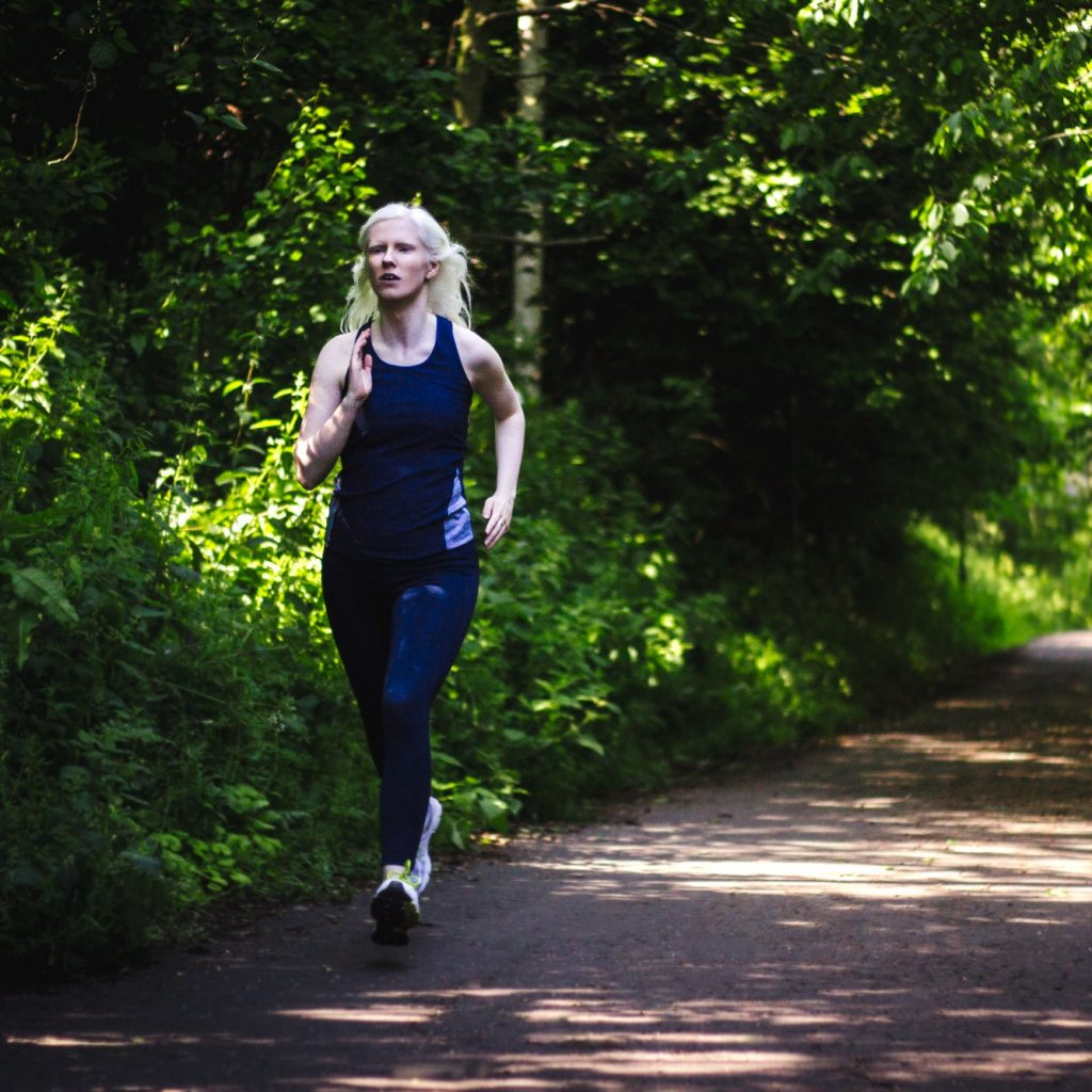 Image of a woman running through a park