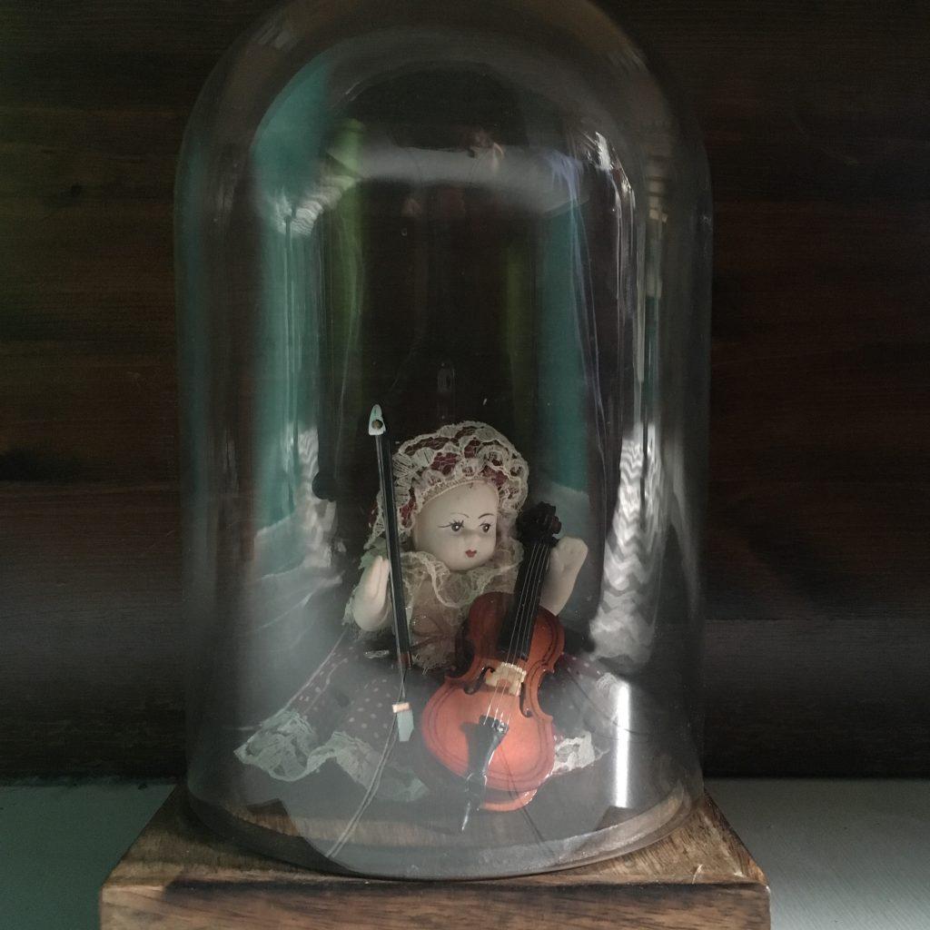 Inside a large glass jar a doll plays a violin