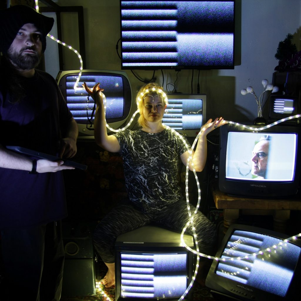 A woman sits on a chair holding string lights in her hands. Around her are old tvs and one of them shows Charles Haywards face. A man stands to her right.