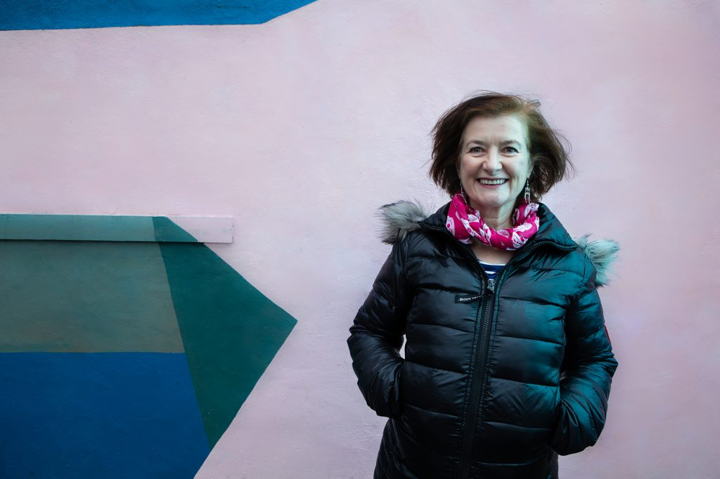 Angela Clerkin - a lady smiling with brown hair in a pink scarf and black puffer jacket