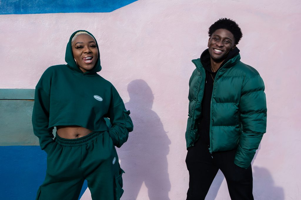 A lady with a green hoodie and traksuit bottoms sticking here tongues out and a man in a green puffer jacket smiling in front of a pink wall