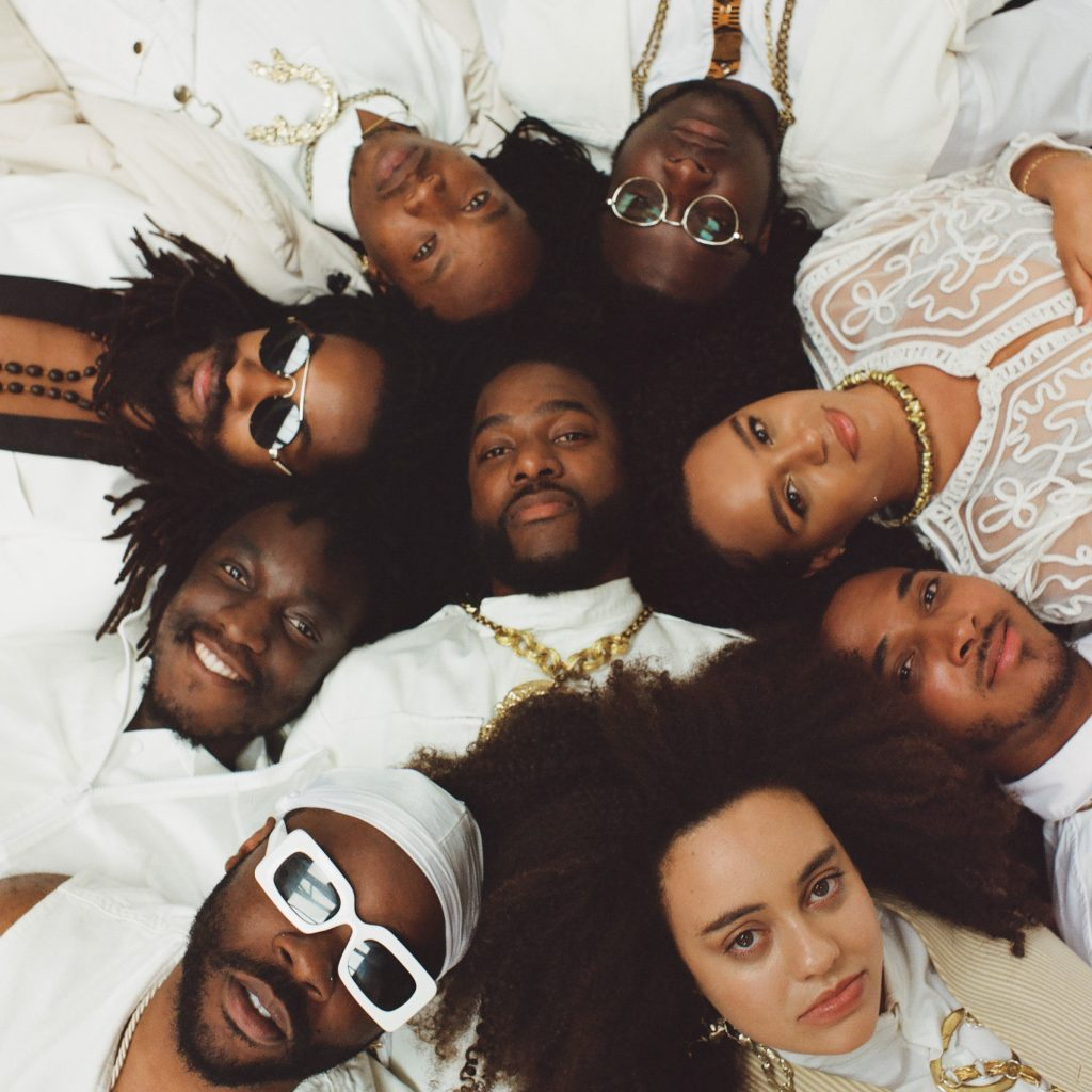 8 people wearing white lying in a circle with one person in the middle